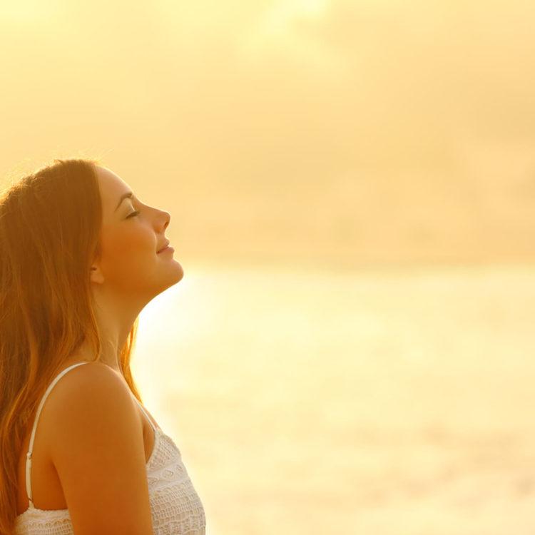 Mulher no por do sol, de perfil, que relaxa e respira o ar fresco